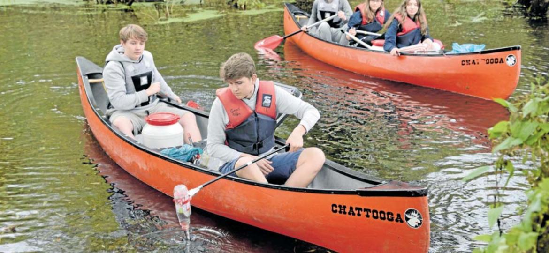 Steuermann Luka hält das Kanu im Plöner Stadt- graben in Position, während Mikko mit dem Greif- arm Plastik- flaschen aus dem Wasser fischt. FOTO: DIS